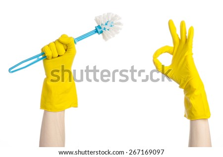 Cleaning the house and cleaning the toilet: human hand holding a blue toilet brush in yellow protective gloves isolated on a white background in studio - stock photo