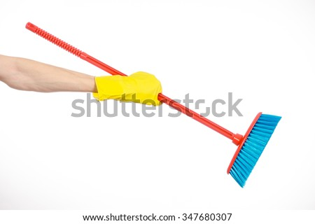 Cleaning the house topic: human hand in yellow rubber gloves holding a red broom isolated on a white background in studio - stock photo