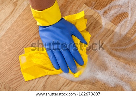 Cleaning the wooden floor by rubber - stock photo