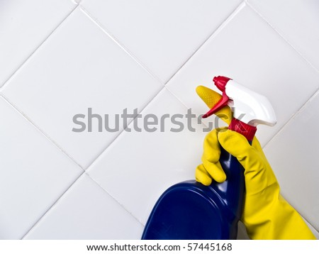 Cleaning washing white tile with spray and yellow glove - stock photo