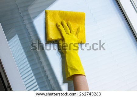 Cleaning windows with special rag in yellow gloves - stock photo
