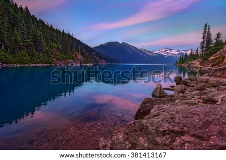 Clear and tranquil water, pink-hued sky, dense trees, and mountains on the horizon - stock photo