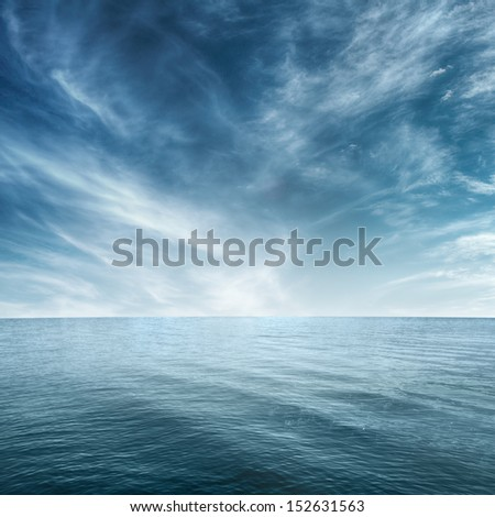 Clear blue sea and cloudy sky over it - stock photo
