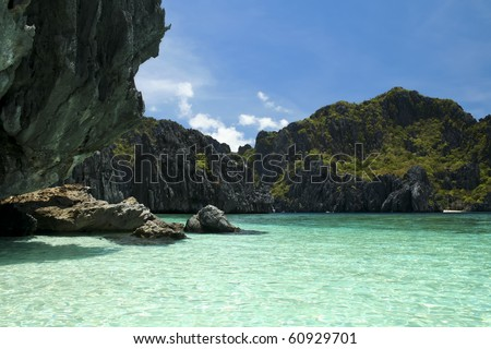clear blue sea lagoon ringed by jagged karst rock formations in el nide palawan island in the philippines - stock photo