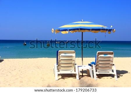 clear blue sky with beach umbrella - stock photo