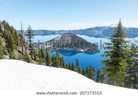 Clear blue water of Crater Lake National Park in Oregon during early spring with some snow left from winter. Wizard Island in the distance. - stock photo