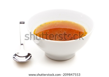 Clear broth with spoons next to it - stock photo