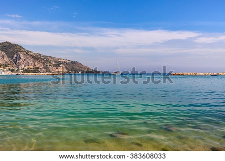 Clear coastal water of Mediterranean sea and small yacht on background of mountain in Menton - small town on French Riviera. - stock photo