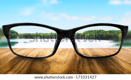 Clear lake in glasses on the background of blurred nature  - stock photo