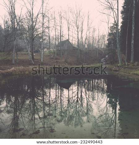 clear morning by small lake with reflections in latvia. Vintage photography effect. - stock photo