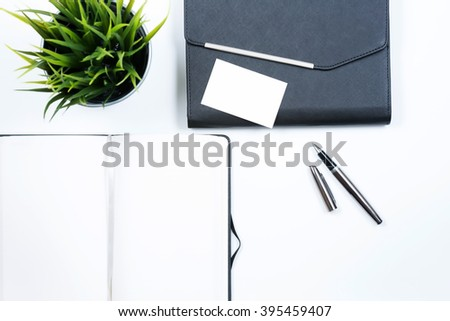 Clear Note Book with clear name card, group of pen and grass in the bucket arrange in flatlay with white background. Selective focus with shallow depth of field. - stock photo