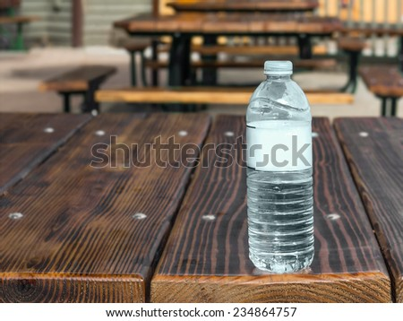 Clear plastic water bottle on outdoor wood picnic table. Outside eating area with row of rustic wooden tables.   - stock photo