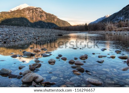Clear river with rocks leads towards mountains lit by sunset - stock photo