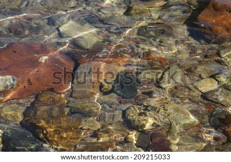 Clear sea water and stones on the floor, low-tide time - stock photo