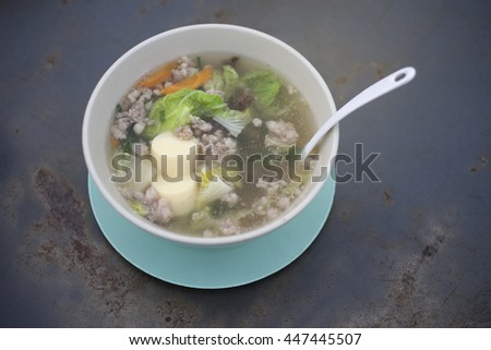clear soup with bean curd and minced pork and vegetable on steel table, thai traditional food,selective focus, filtered image - stock photo