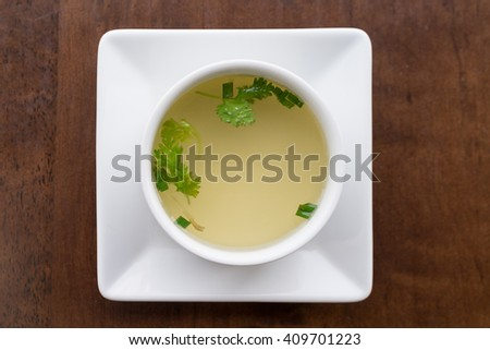 Clear soup with coriander in a white bowl, Top view. - stock photo
