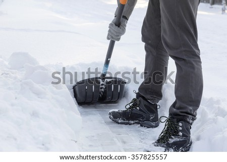 clearing snow with a shovel from sidewalk after blizzard - stock photo