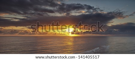 Clearing storm clouds give way to a dramatic sunset off the Oregon coast - stock photo