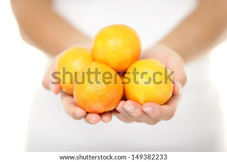Clementine. Clementines that are a variety of mandarin oranges citrus fruits. Woman showing handful. Shot in studio with shallow depth of field isolated on white background. - stock photo