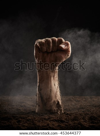 Clenched fist of dead climbs out of the ground - stock photo