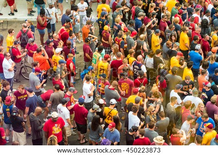 CLEVELAND, OH - JUNE 22, 2016: Cavs fans mingle in the streets wearing team colors and apparel in anticipation of the Cleveland Cavaliers' NBA championship parade. - stock photo