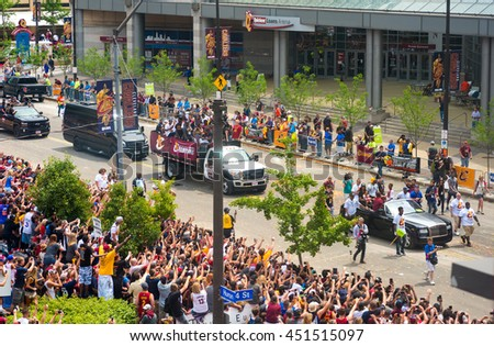 CLEVELAND, OH - JUNE 22, 2016: LeBron James (in yellow baseball cap) rides with his family past cheering crowds in the Cleveland Cavaliers' NBA championship parade. - stock photo