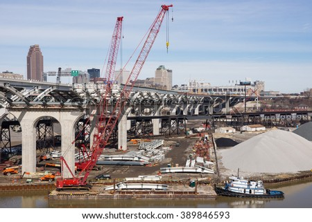 CLEVELAND, OH - MARCH 12: A tugboat on the Cuyahoga River positions a barge with a crane used in the construction of the second span of a new innerbelt bridge in Cleveland, Ohio on March 12, 2016 - stock photo