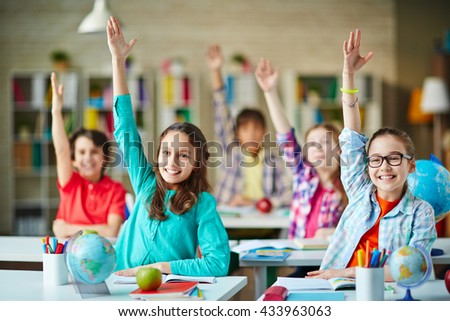 Clever girls and boys raising hands to answer the question - stock photo