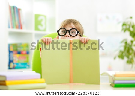 clever little child behind of open book indoor - stock photo