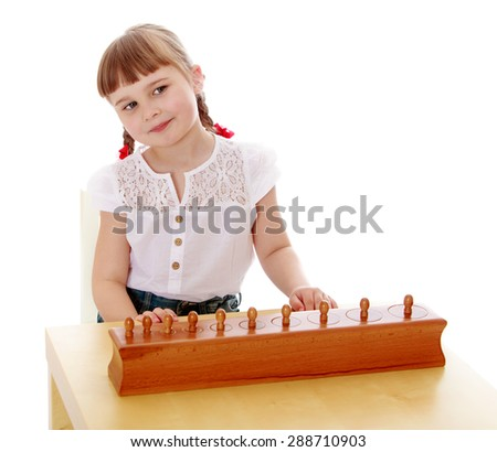 Clever Little girl is working with the material in the Montessori kindergarten-Isolated on white background - stock photo