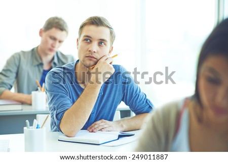 Clever student thinking of idea of essay - stock photo