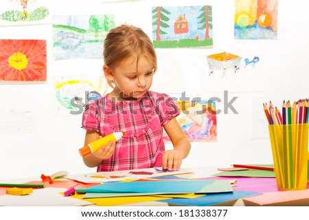 Clever 4 years old girl holding glue by the table in art lesson in kindergarten  - stock photo
