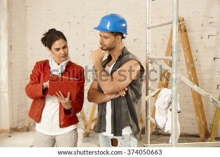 Client and contractor talking at renovation site, using tablet computer. - stock photo