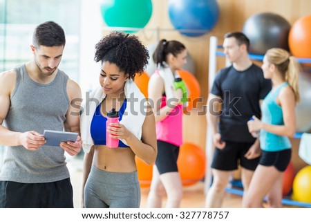 Client and trainer looking at tablet pc at the gym - stock photo