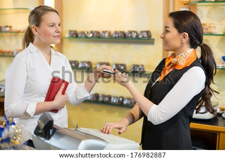 Client at shop paying at cash register with saleswoman - stock photo