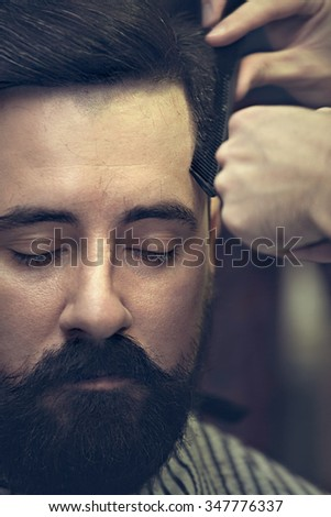Client Barbershop while cutting hair. Image of stylish hipster man with a mustache and beard that makes the cut. - stock photo