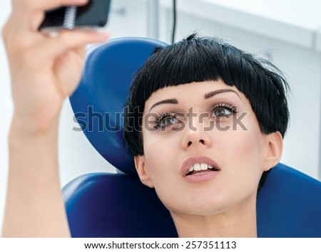 Client dentist makes a photo of herself on her cell phone in the dental chair. Dentist makes the process of treatment of a beautiful young girl. - stock photo