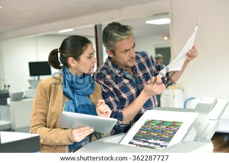 Client in printshop controlling work before final printing - stock photo