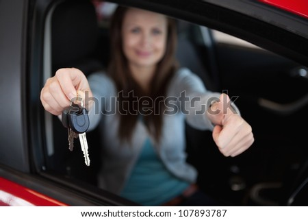 Client sitting in her car while holding car keys in her car - stock photo