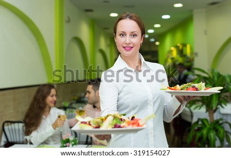 Clients at table and charming waitress with plates in cafe - stock photo