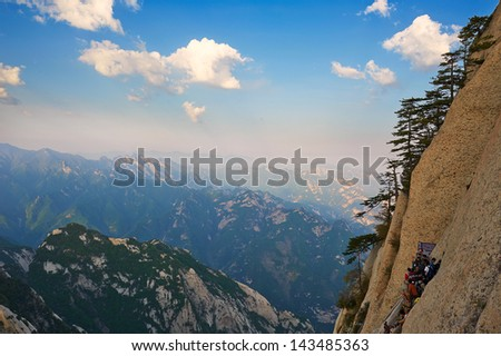 Cliff and multipeaked mountains.The image taken in china's shanxi province xian city huashan scenic spot. Time is in 2013 at the beginning of May.The picture is the sky path along the cliff. - stock photo