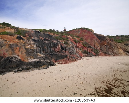 Cliff at beach with watchtower and sky in background. - stock photo