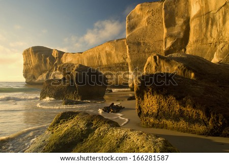 Cliff formations at Tunnel Beach, sculpted cliffs seen from Tunnel Beach in first morning light, Otago, South Island, New Zealand - stock photo