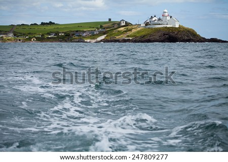 Cliff in Ireland, view from the boat. Cold Atlantic ocean, travel to Ireland with fisherman.rocks subjected to erosion, water undermines land. Seascape with sky and flying seagull.Turquoise blue water - stock photo