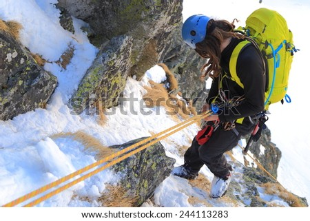 Climber abseiling snow covered slope in winter - stock photo
