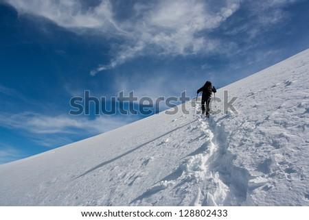 Climber ascending snowy peak - stock photo