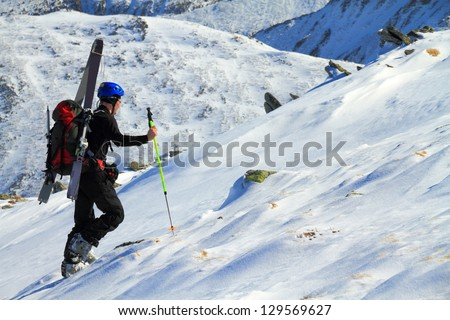 Climber carrying skies and ascending a snow covered mountain slope - stock photo