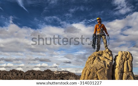 Climber coils ropes on the summit. - stock photo