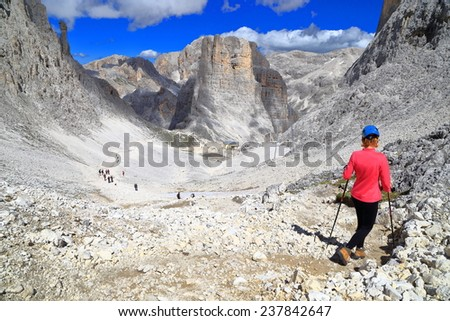 Climber descending a large valley to the Vajolet towers, Catinaccio massif, Dolomite Alps, Italy - stock photo