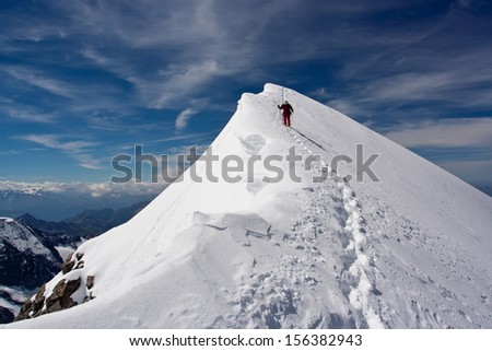 Climber descending snowy peak at mountains - stock photo